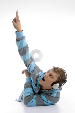 Laying young man with headphone indicating upward stock photo, Laying young man with headphone indicating upward with white background by Imagery Majestic