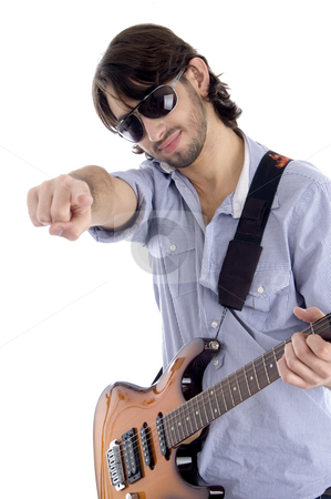 Young guitarist with pointing finger stock photo, Young guitarist with pointing finger against white background by Imagery Majestic