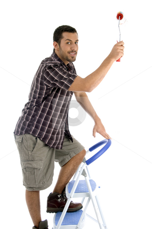 Young guy holding painting brush stock photo, Young guy holding painting brush on an isolated white background by Imagery Majestic