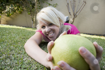 Caucasian woman posing with sweet lime stock photo, Caucasian woman posing with sweet lime on the grass by Imagery Majestic