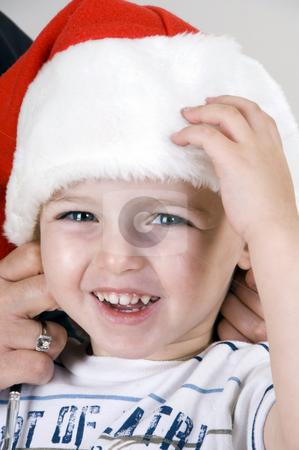 Portrait of cute little boy stock photo, Portrait of cute little boy with christmas hat by Imagery Majestic
