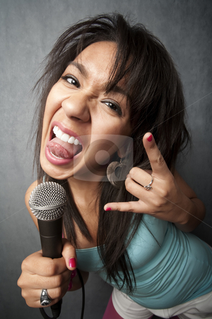 Beautiful Young Singer Sticking Out Her Tongue stock photo, Pretty young singer with a large microphone by Scott Griessel