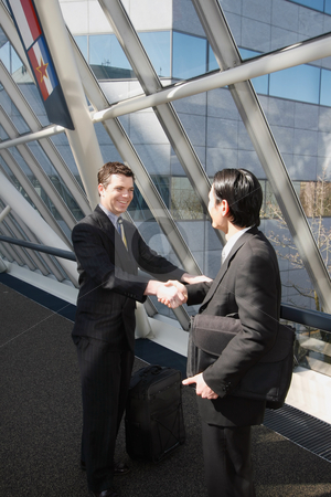 Let's Shake on It stock photo, Two businessmen smiling and shaking hands in an office lobby by Orange Line Media
