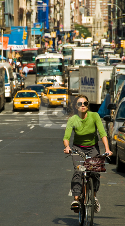 New York City traffic stock photo, Woman on bike with dense traffic behind.  Mid-town NYC by Ron Greer