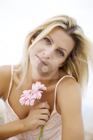 natural beauty stock photo, Portrait of young woman outdoors with flower by Liv Friis-Larsen