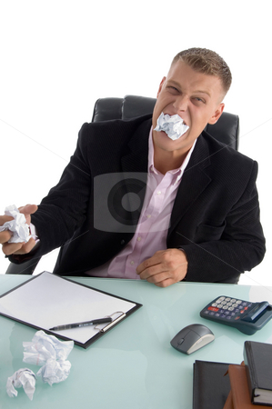 Frustrated businessman with paper in his mouth stock photo, Frustrated businessman with paper in his mouth on an isolated background by Imagery Majestic