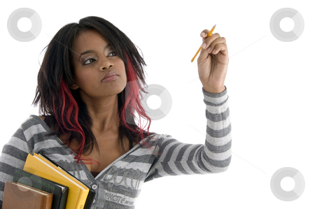 Girl with books and looking to pencil stock photo, Girl with books and looking to pencil against white background by Imagery Majestic