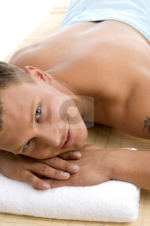 Young male lying on mat ready to take spa treatment stock photo, Young male lying on mat ready to take spa treatment on an isolated white background by Imagery Majestic