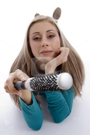 Laying woman holding roller comb stock photo, Laying woman holding roller comb on an isolated white background by Imagery Majestic