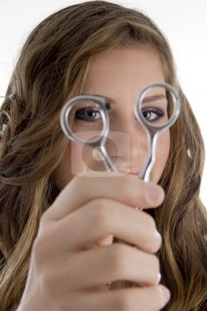 Girl looking into scissors stock photo, Girl looking into scissors on an isolated background by Imagery Majestic