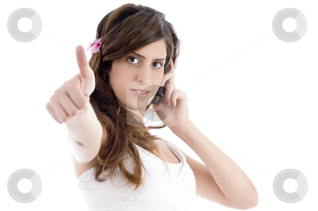 Woman with cell phone showing approval sign stock photo, Woman with cell phone showing approval sign on an isolated background by Imagery Majestic