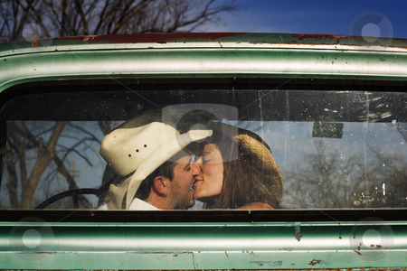 Cowboy Kiss stock photo, Cowboy and girlfriend kissing in through the back window of a pickup truck by Scott Griessel