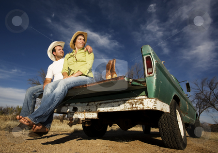 Cowboy and woman on pickup truck stock photo, Portrait of Cowboy and woman on pickup truck bed by Scott Griessel