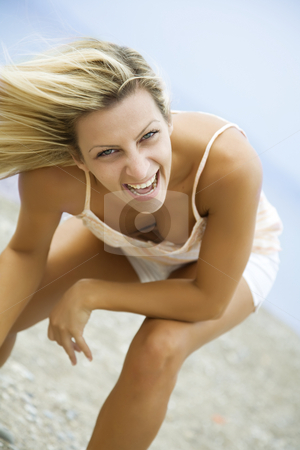 Ecstatic stock photo, Young female on the beach in a summer dress, laughing by Liv Friis-Larsen