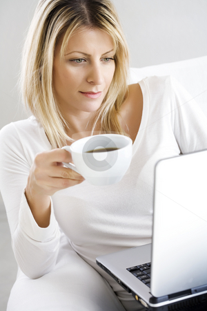 Coffee and laptop stock photo, Young woman sitting in the couch with a cup of coffee and laptop by Liv Friis-Larsen