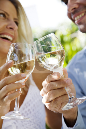 Wine in the garden stock photo, Young couple enjoying a glass of white wine in the garden by Liv Friis-Larsen