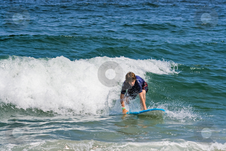 Teenage Surfer stock photo, A teenage boy surfing in the ocean by Stephen Bonk