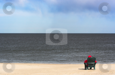 Alone on the beach stock photo, A young person in a hooded red sweatshirt sitting alone on a chair in the sand at the beach. The hood of the sweatshirt is on indicating it is a chilly day. The person is looking out over the ocean. by Stephen Bonk