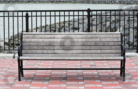 Park Bench stock photo, A park bench at a reservoir. The bench is on a brick patio and the background is water and rock. by Stephen Bonk