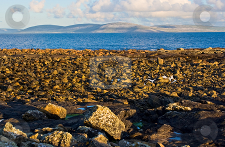 Galway Bay and Burren stock photo, Galway Bay in Ireland with The Burren across the bay. Photo is layered from front to back with Rocks, Galway Bay, The Burren, and sky. by Stephen Bonk