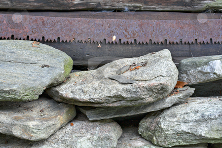 Rust and Rocks stock photo, A rusty old saw blade hanging above a pile of stacked rocks. by Stephen Bonk