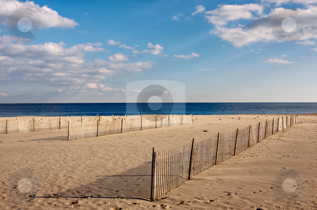 Fences on the Beach stock photo, Wooden fences on the beach, The fences are on the sand in the foreground with the ocean and sky above. by Stephen Bonk