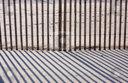 Fence, Sand, and Shadows stock photo, An abstract image of a fence on a beach with diagnol shadows by Stephen Bonk