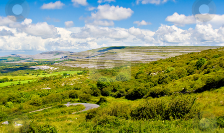 Ireland Landscape stock photo, Landscape of County Clare, Ireland. Green fields, trees, and a winding road in foreground and The Burren and sky in the background. by Stephen Bonk
