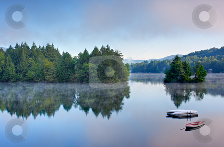 Mountain Lake in the Morning stock photo, A lake in the early morning with fog on the water. A boat and dock are in the foreground. by Stephen Bonk