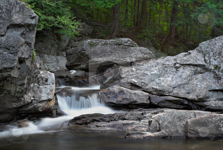 Waterfall and forest stock photo, A small waterfall over rock with a forest in the background by Stephen Bonk