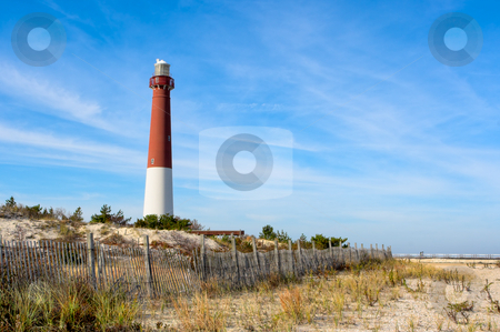 Lighthouse on the Beach stock photo, A lighthouse on the beach. There is also an old wooden fence on the beach in this landscape. This is Barnegat Lighthouse, nicknamed