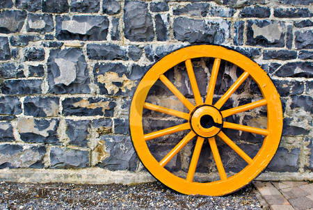 Wooden Wagon Wheel stock photo, An old yellow wooden wagon wheel leaning against a stone wall by Stephen Bonk