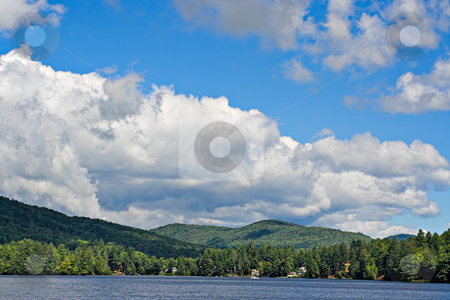 Clouds Over the Mountains stock photo, Mountains at the shoreline of a lake with large cumulus clouds in the sky above. by Stephen Bonk