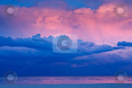Beach Sunset stock photo, A beach scene in the evening at sunset. There are stormy clouds in the sky and the last rays of sunlight are lighting some of the clouds. by Stephen Bonk