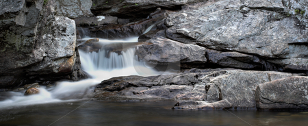 Waterfall Panorama stock photo, A small waterfall over rock in panorama format by Stephen Bonk