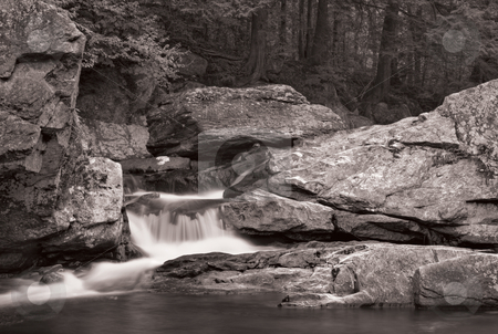 Waterfall and forest in B&W stock photo, A small waterfall over rock with a forest in the background. Photo is in black and white. by Stephen Bonk