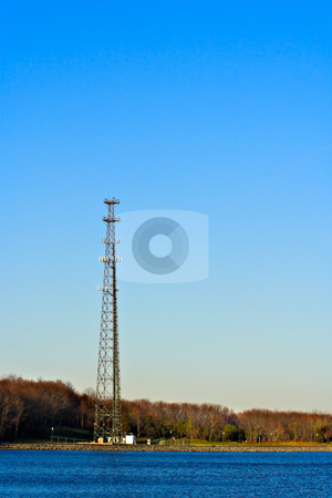 Communication Tower stock photo, A communication tower at the edge of a lake with a clear blue sky as the background. Photo is in vertical or portrait format. by Stephen Bonk
