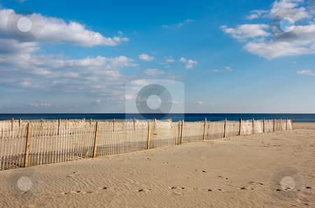 Fence on the Beach stock photo, A wooden fence on the beach, The fence is on the sand in the foreground with the ocean and sky above. by Stephen Bonk