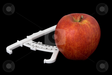Apple and Caliper stock photo, Apple and body fat calipers by Stephen Bonk