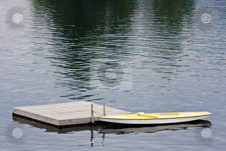 Docked Boat on Lake stock photo, A small yellow boat tied to a dock on a lake. by Stephen Bonk