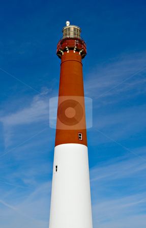Lighthouse stock photo, A red and white lighthouse against a blue sky. by Stephen Bonk