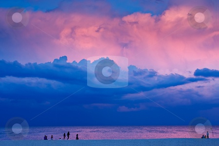 Evening Beach Scene stock photo, A beach scene in the evening at sunset. There are people on the beach with a dramatic stormy sky overhead. The last rays of sunlight are lighting some of the clouds. by Stephen Bonk