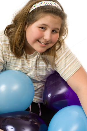 Birthday Balloons stock photo, A young girl surrounded by balloons is smiling, isolated against a white background by Richard Nelson