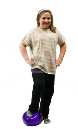 Accomplishment stock photo, A young girl with one foot on a ballon and her arms on hips, isolated against a white background by Richard Nelson