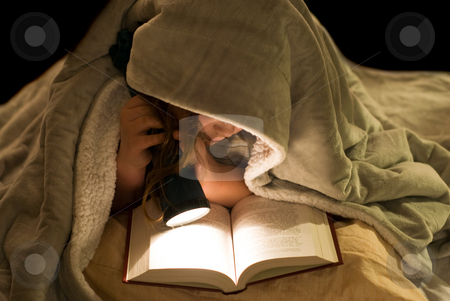 Reading Under The Covers stock photo, A young girl reading a book under the covers with a flashlight by Richard Nelson