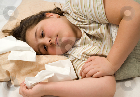 Sick Child stock photo, A young girl not feeling well is lying in bed with tissues around her by Richard Nelson