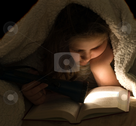 Child Reading In The Dark stock photo, Closeup view of a young girl reading a book in the dark, with a flashlight by Richard Nelson