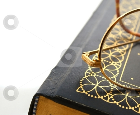 Reading Glasses and Book stock photo, A pair of reading glasses sitting on top of a book. by Karma Shuford