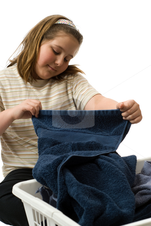 Child Doing Chores stock photo, A young girl folding some clean bath towels, isolated against a white background by Richard Nelson