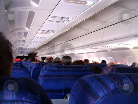 Airplane Interior stock photo, Passengers eagerly awaiting takeoff on a commercial jet. by Todd Arena